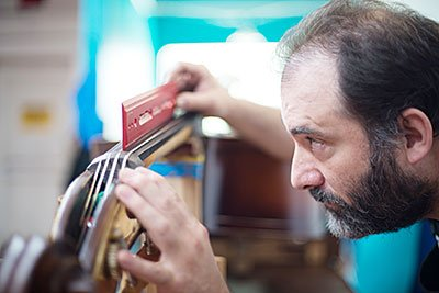 Photo of Ted adjusting the strings on an upright bass in our Maplewood store workshop.