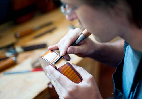 Photo of a luthier working on a violin in our St. Louis (Maplewood) workshop.